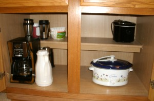 Lower cabinet...coffee maker and accoutrements, and mini and maxi crocks.